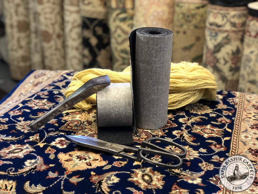 Deux échantillons de sous-tapis, avec un peigne de tapis, une cisaille, et un fil de laine.