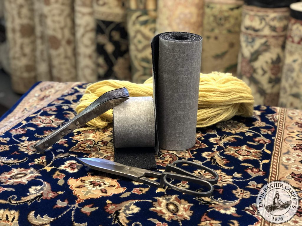 Two area rug gripper samples alongside a rug beating comb, a pair of shearing scissors and strand of yarn.
