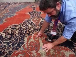 An inspector examining a persian rug